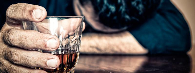Hombre joven borracho en la barra del bar, con una copa de alcohol entre las manos y la cabeza sobre el otro brazo.
